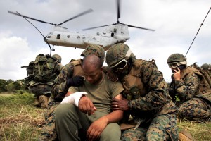 Corpsmen shield a simulated casualty from the rotor wash of a CH-46E Sea Knight helicopter